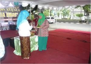 Ketua Yayasan Kucala menyerahkan tumpeng kepada Dr.Ratna Wijatanti,M.kes.